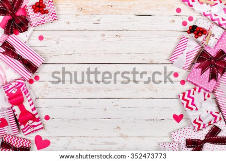 Wooden background with copyspace with border of decorative gifts - stock photo