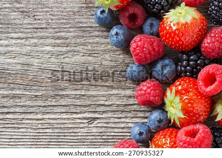 wooden background with fresh berries, top view, horizontal - stock photo