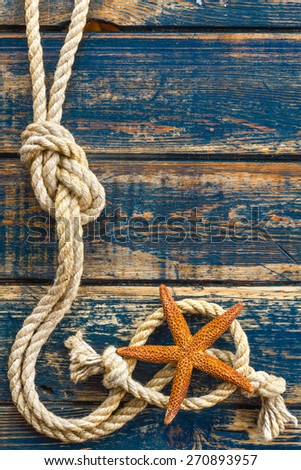 Wooden background with starfish and marine rope - stock photo