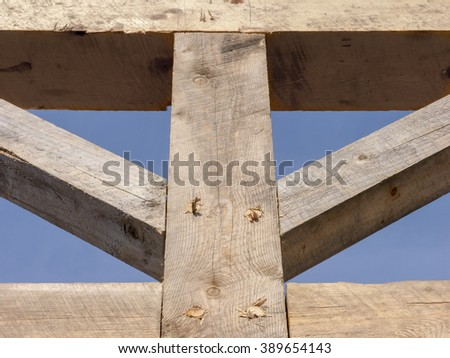 Wooden Barn Frame Detail: A wood timber frame detail showing the post and upper beams with knee braces held together by wood pegs  - stock photo