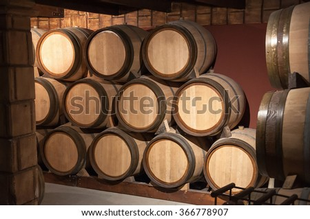 Wooden barrels for wine in the cellar - stock photo