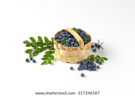 wooden basket of freshly picked blueberries accompanied by blueberry twigs - stock photo