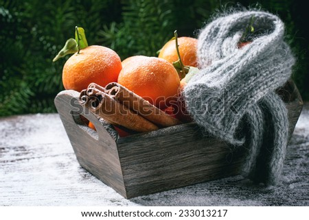 Wooden basket with tangerines, cinnamon sticks and scarf over wooden background with snow and cone.  - stock photo