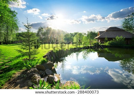 Wooden bathhouse near lake in the evening - stock photo