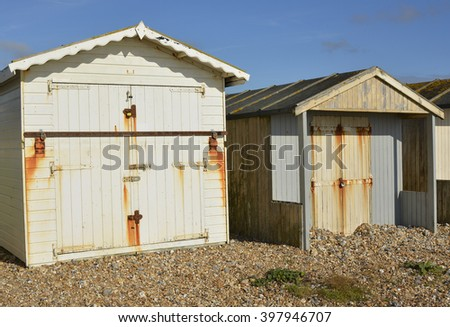 Wooden beach huts on shingle beach at Lancing, Near Brighton, West Sussex, England - stock photo