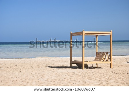 Wooden beach lounge chairs along the shoreline - stock photo