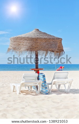 Wooden beach umbrella and sun bed on the beach, in the background a woman sunbathes. - stock photo