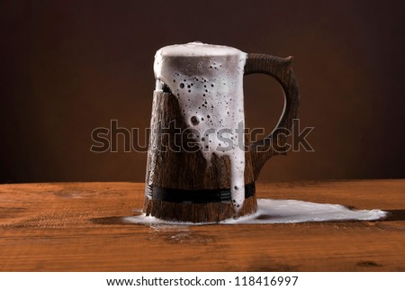 Wooden beer mug with foam on the dark red background. - stock photo