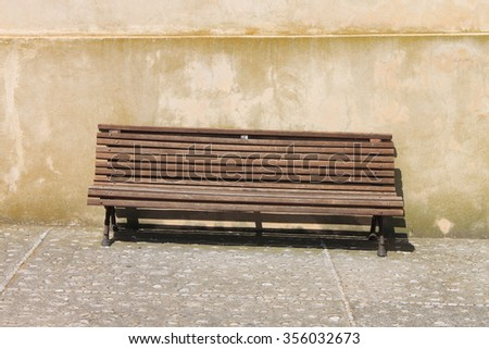 Wooden bench along the city street - stock photo