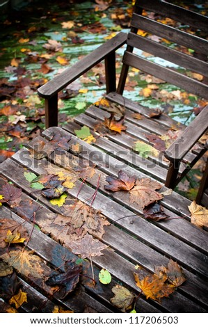 Wooden bench and table covered with fallen autumn leaves - stock photo