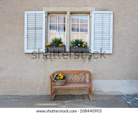 Wooden Bench for Rest under the Window - stock photo