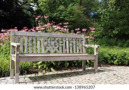 wooden bench in a beautiful garden - stock photo