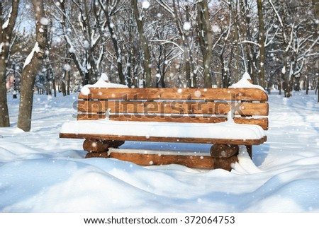 Wooden bench in the winter city park. Bright sunny day and snow. - stock photo