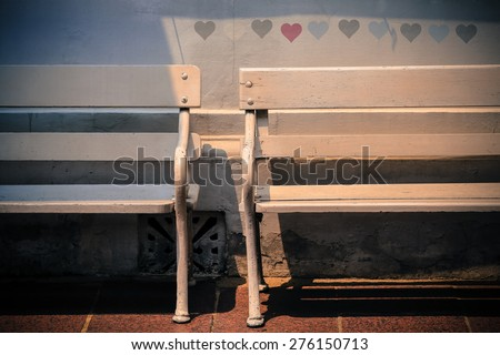 wooden bench near the street with love shadow behind - stock photo