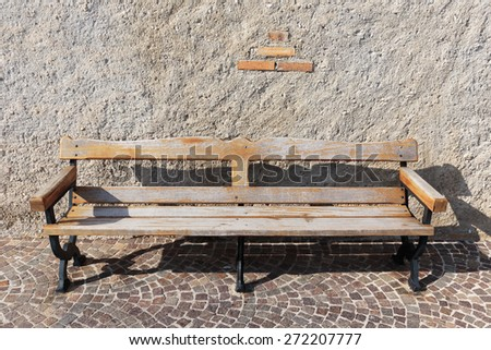 Wooden bench on a cobbled street - stock photo
