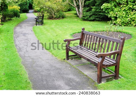 Wooden Bench on a Path in a Beautiful Green Park - stock photo