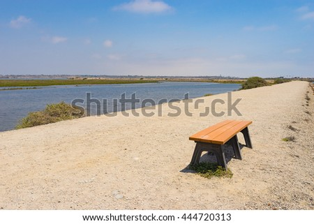 Wooden bench on sandy park trail near waterway. - stock photo