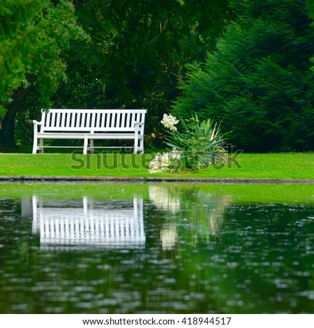 wooden bench on shore of picturesque lake - stock photo