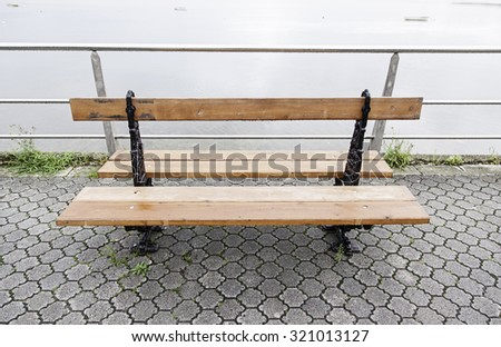 Wooden bench on the beach, detail of a bench to rest - stock photo
