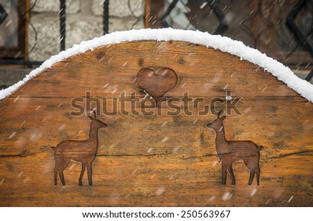 Wooden bench with carved deers and heart in snowfall - winter love Saint Valentines day postcard background - stock photo