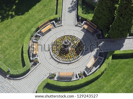 Wooden benches in the flowering garden. View from above. - stock photo