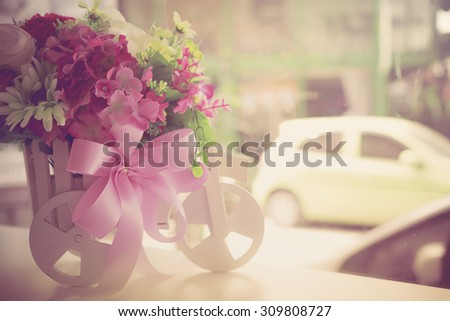 Wooden bicycle toy for decorative with artificial flowers - stock photo