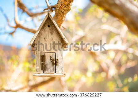 Wooden birdhouse hanging on the tree with blurred background - stock photo