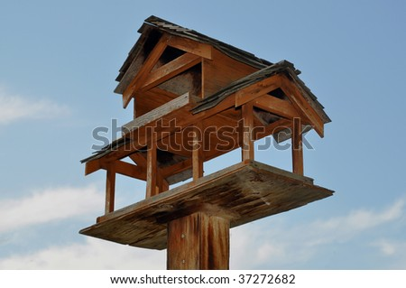 Wooden birdhouse high up in the bright blue sky - stock photo