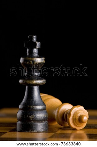 Wooden black King standing next to defeated white Queen on chessboard with black background. - stock photo