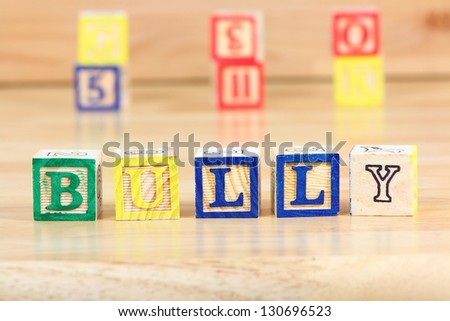 Wooden blocks with letters. Children educational toy concept - school bullying emotional distress - stock photo