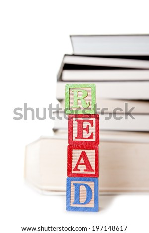 Wooden blocks with letters on them in front of a stack of books. - stock photo