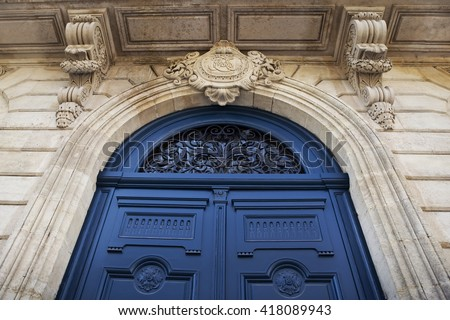 Wooden blue door on the stoned facade of a French mansion - stock photo