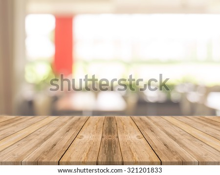 Wooden board empty table in front of blurred background. Perspective brown wood over blur in coffee shop - can be used for display or montage your products.Mock up your products.Vintage filter. - stock photo