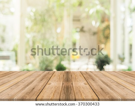 Wooden board empty table in front of blurred background. Perspective brown wood over blur in coffee shop - can be used for display or montage your products.Mock up for display of product. - stock photo
