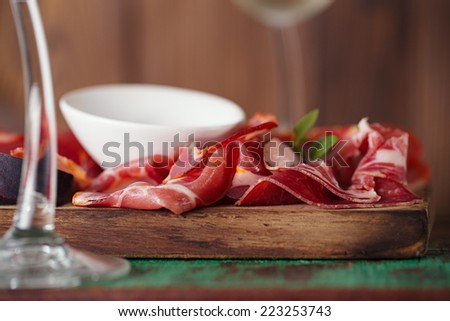 wooden board of Assorted Cured Meats, olive oil and glasses of white wine on vintage stool - stock photo