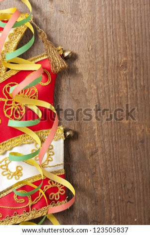Wooden board with colorful streamers and carnival hat - stock photo