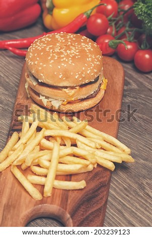 Wooden board with hamburger and fries on it - stock photo