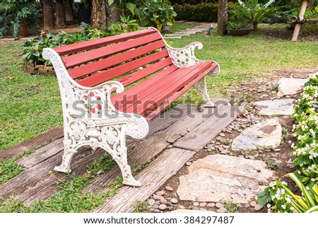 Wooden board with metal bench in the garden - stock photo