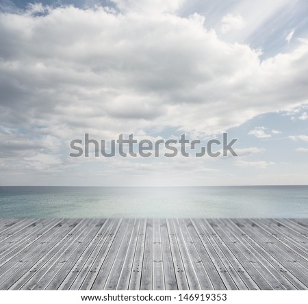 Wooden boards leading out to a bright horizon on a sunny day - stock photo