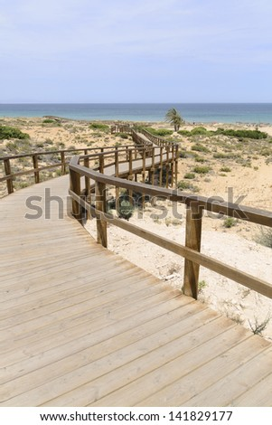 Wooden Boardwalk at Arenales del Sol beach - stock photo