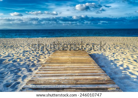 wooden boardwalk on the sand in hdr tone mapping effect - stock photo