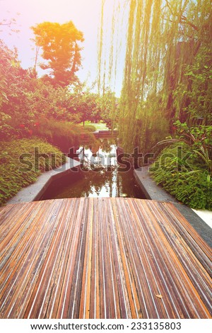 Wooden boardwalk overlooking a beautiful pond in the early morning - stock photo