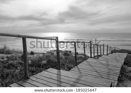 Wooden boardwalk to the beach - stock photo