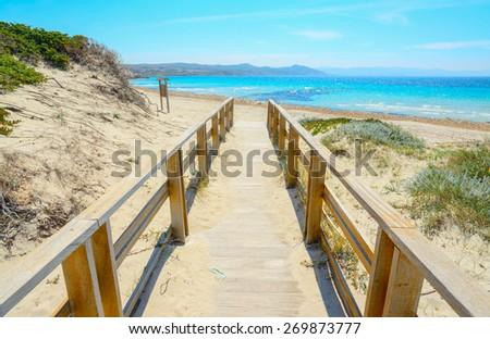 wooden boardwalk to the beach in Capo Testa, Sardinia - stock photo