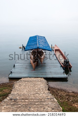 Wooden boat house in the early morning with fog. - stock photo