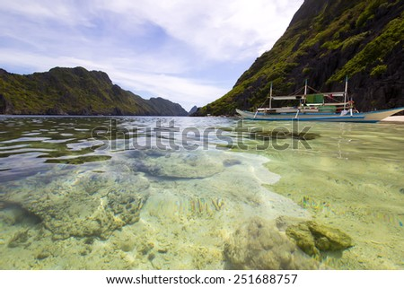 wooden boat in a bay surrounded by cliffs - stock photo
