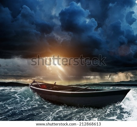 Wooden boat in a stormy sea  - stock photo