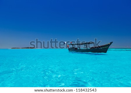 wooden boat in stunning turquoise water - stock photo