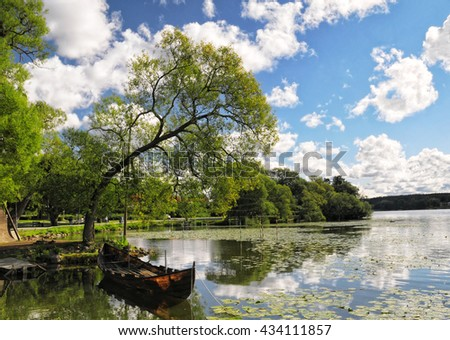 Wooden boat moored at Malaren lake shore under curved tree, Sigtuna, Sweden - stock photo