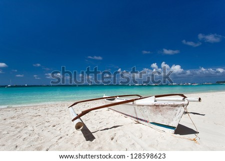 Wooden boat on tropical beach with white sand - stock photo